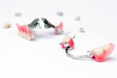 a set of removable clasp prostheses with supporting metal-ceramic and metal crowns on the upper and lower jaws on white background Archivio Fotografico
