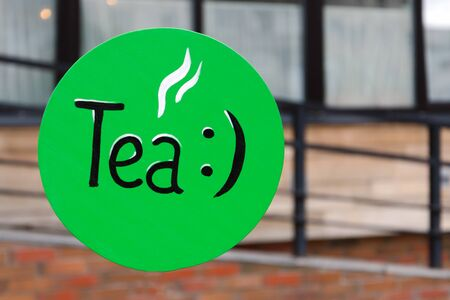 green retro outdoor tea sign. pointer in the morning on the street