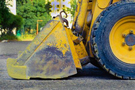 Schaufel und Räder von schweren Baumaschinen. Seitenansicht. gelber Metalleimer mit Kratzern. schmutziger Traktor nach dem Bau. zum Konzept. Baumaschinen