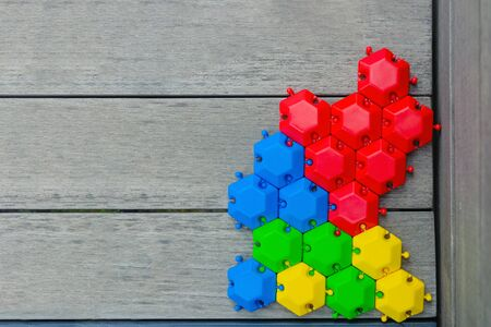 game puzzle of multi-colored hexagons assembled on a wooden gray background. green blue red yellow