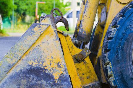 piccola benna gialla del caricatore del bulldozer. vecchio metallo graffiato. concetto di lavoro di costruzione Archivio Fotografico