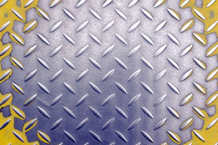 a metallic old worn plate with a diamond pattern and old yellow paint. background