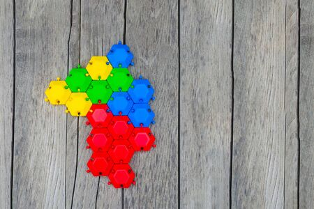 game puzzle of multi-colored hexagons assembled into one. concept of unity, support, strong relations. wooden background. copy space