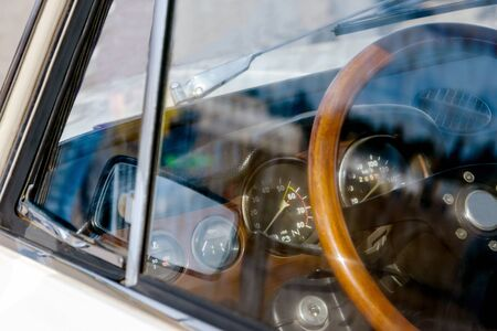 view of the steering wheel and dashboard of a car of the 70s. on glass the reflection of the mirror in sunny weather 免版税图像