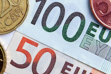 50 and 100 euros close-up. Euro cents are located on the sides. investment concept. banking
