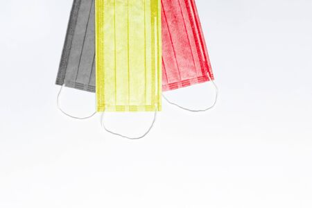 on top are 3 medical masks of black, yellow and red colors on a light background. masks are collected in the flag of Belgium. medicine concept in belgium. coronavirus outbreak in Belgium. Pandemic in Belgium. copy space. flat lay