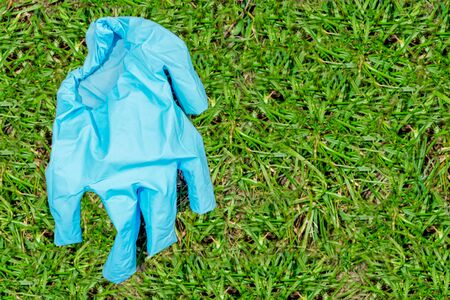 The blue used medical glove lies on the left on the green grass. concept of protecting a person from coronavirus. protection of doctors against the virus. Copy space. Flat lay 免版税图像