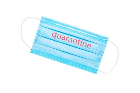 blue medical face mask with the inscription quarantine isolated on a white background. global quarantine concept. flat lay 免版税图像