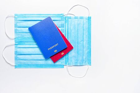 two foreign passports of blue and red colors are on medical masks on a light background. world quarantine concept. Flat Lay. Copy space