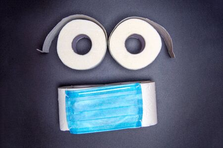 toilet paper rolls are laid out in the form of an emoticon with a blue medical face mask. on a black background. virus outbreak concept. coronavirus news