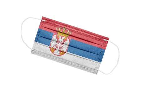 Medical mask with flag of Serbia isolated on white background. The concept of a pandemic in Serbia. Coronavirus outbreak attribute in Serbia. Medicine in Serbia.