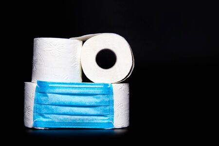 rolls of white toilet paper with a blue medical face mask are on a black background. coronavirus outbreak panic concept