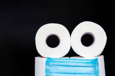 toilet paper rolls with a medical mask folded in the form of an emoticon, on a black background. concept of panic during coronavirus. copy space 免版税图像