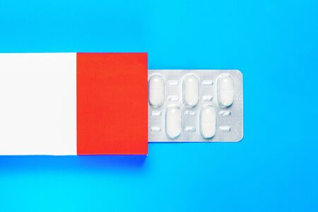 blister pack with pills in a red-white box on a blue background. copy space. flat lay 免版税图像