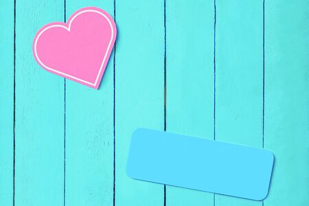 pink heart on a blue wooden background and a blue plate. copy space. Background for weddings, valentines day. romantic background