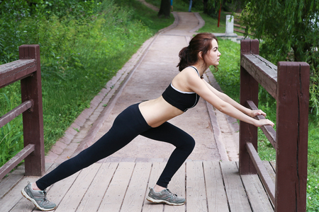 Young woman doing gymnastics outdoors in the afternoon. In the park.