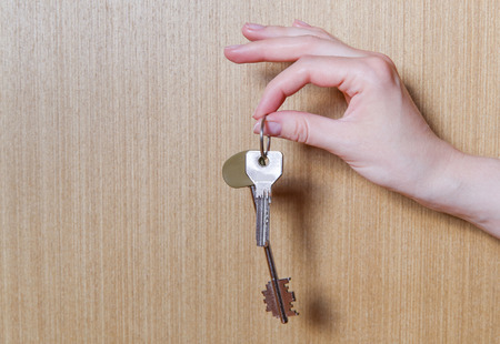 women's hand: Womens hand holding two keys from the apartment. Wooden background. Stock Photo