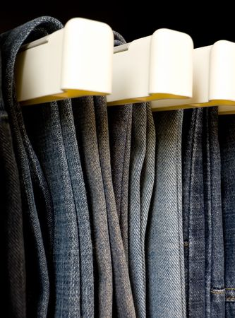 Jeans hanging in closet Stock Photo