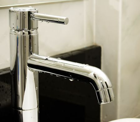 Chrome Water tap with drops of water on it.