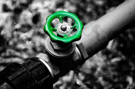 Green water valve and black&white background. photo