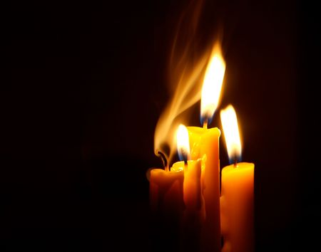 Four Candles isolated over dark background. photo
