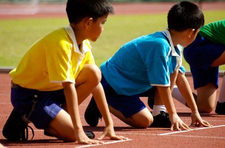 ni�o corriendo: Los ni�os se preparan para comenzar a publicar en highschool acontecimiento deportivo. Foto de archivo