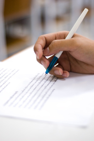 Hand holding a pen over a paper.Shallow depth of field. Stock Photo