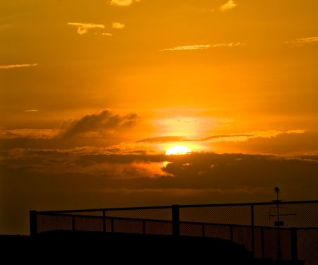 Photos of sunset with fences in the foreground.