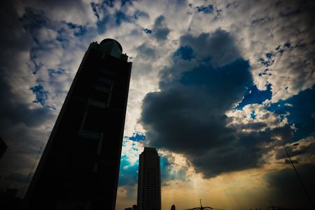 Blue sky, white clouds with building in the foreground. Stock Photo