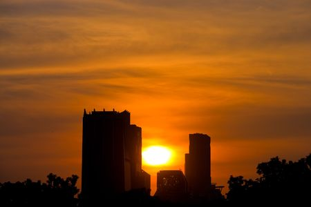 Picture of buildings with sun setting in the background. Stock Photo