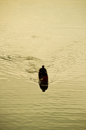 A man rows a wooden classical boat in a river.