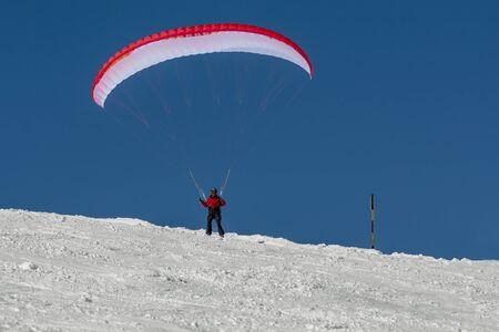 Gleitschirm im Schnee Berg satrt Standard-Bild