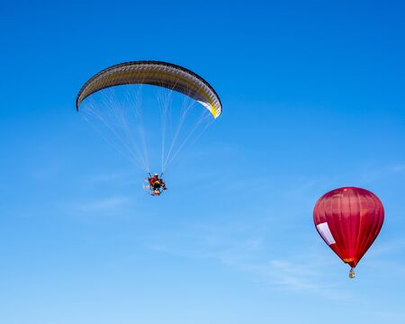 Baloon with moto glider in the blue sky red Imagens