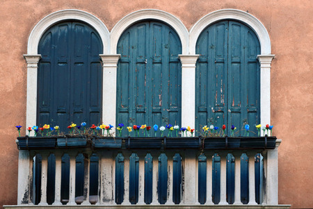 parapet: Balcony with three-light windows, parapet and fake flowers in Venice