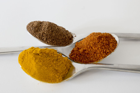 Spices in teaspoons on a white background
