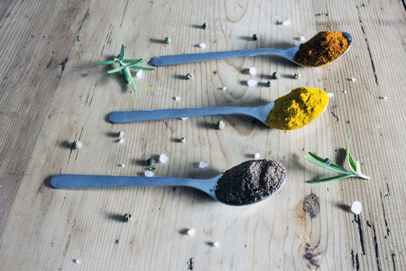 flavour: Spices in teaspoons on a wooden background