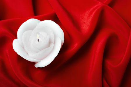 Candle in the form of a rose against silk photo