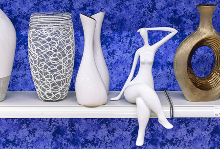 Women's ceramic statuette on a shelf with vases. Archivio Fotografico