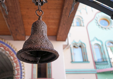 Ancient iron bell on the background of a wooden structure.