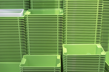 Plastic green containers stacked in several rows.