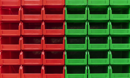 Plastic green and red containers are stacked in several rows.