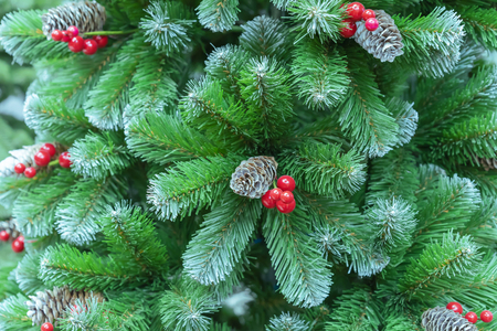 Green Christmas tree with red berries and pine cones.