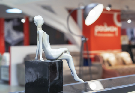 Silvery statuette of a woman on a black cube.
