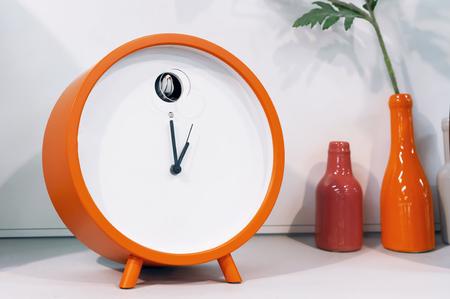 Orange cuckoo alarm clock in modern interior.