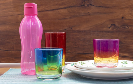 Glasses from multi-colored glass and a pink bottle for cold drinks.