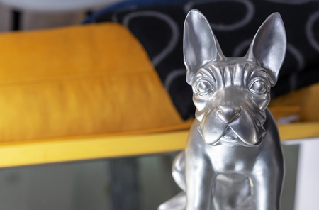 Silver statuette of a dog in the home interior.
