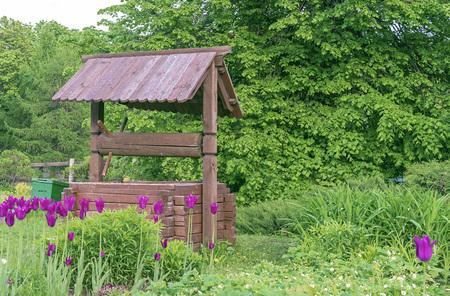 Pozzo di legno nel villaggio. Pozzo di legno sullo sfondo del fogliame verde.