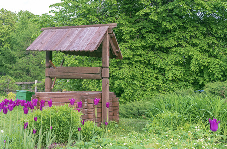 Wooden well in the village. Wooden well on the background of green foliage.