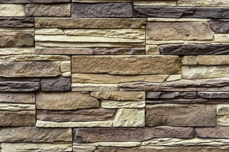 Texture of the stone wall. Panel of stones for finishing the facade of the building and interior design of the house. Background for design and decoration. Imagens