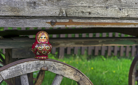Nested doll on the background of an old wooden cart. Matryoshka is a national Russian souvenir. Imagens